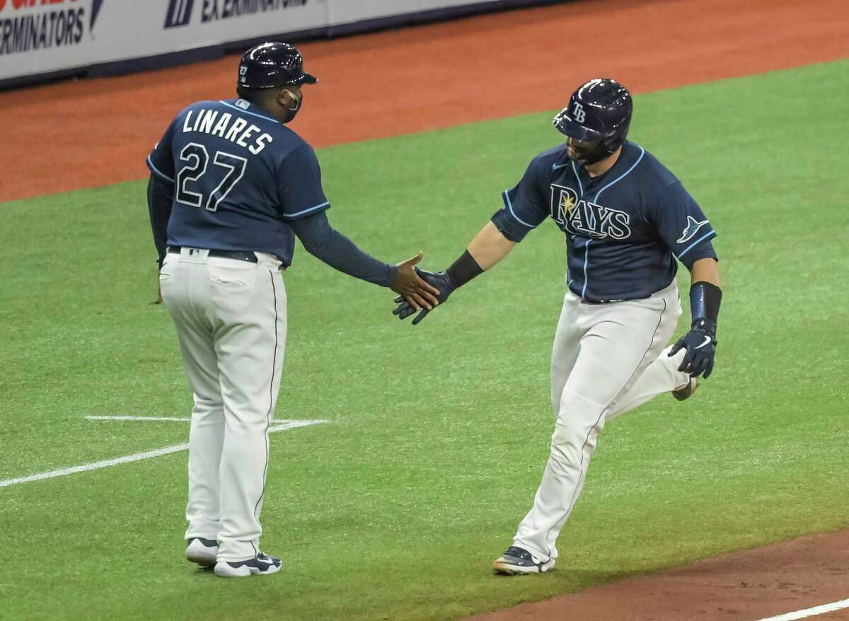 Tampa Bay Rays third base coach Rodney Linares (27) congratulates Mike Zunino on a solo home run off Oakland Athletics starter Cole Irvin during the fifth inning of a baseball game Wednesday, April 28, 2021, in St. Petersburg, Fla. (AP Photo/Steve Nesius)