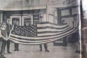 Holding the flag flown over the Capitol in Washington, D.C., are Adams Elementary School students, from left, Janeen Mathison, Daniel Anthony, Shelly Bruett, Greg Putalik, Cindy Shook, Rebecca Bleisner and Jean Dennett. March 1967