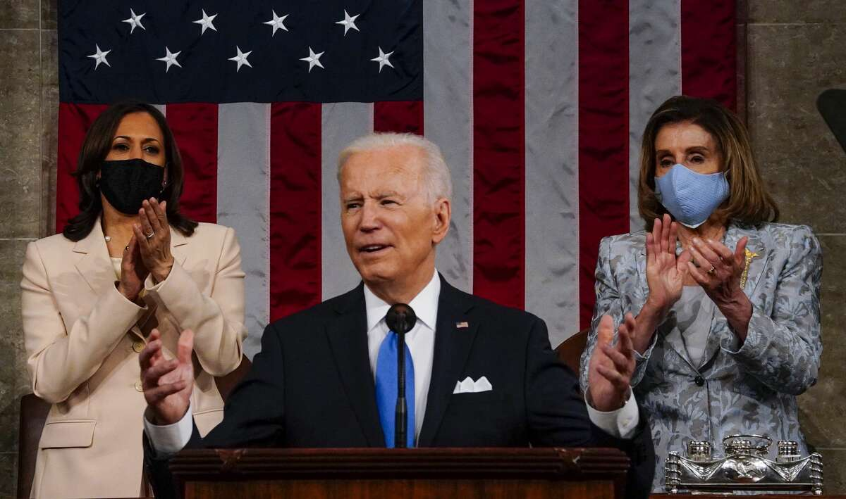 WASHINGTON, DC - APRIL 28: U.S. President Joe Biden addresses a joint session of Congress as Vice President Kamala Harris (L) and Speaker of the House U.S. Rep. Nancy Pelosi (D-CA) (R) look on in the House chamber of the U.S. Capitol April 28, 2021 in Washington, DC. On the eve of his 100th day in office, Biden spoke about his plan to revive America's economy and health as it continues to recover from a devastating pandemic. He delivered his speech before 200 invited lawmakers and other government officials instead of the normal 1600 guests because of the ongoing COVID-19 pandemic. (Photo by Melina Mara-Pool/Getty Images)