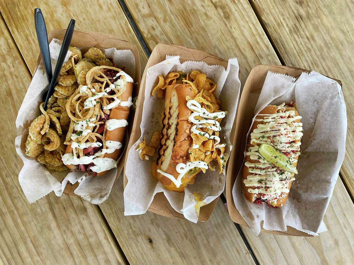 Hot dogs at The Dogfather include, from left, The Brat (beer bratwurst, spicy mustard, horseradish crema, cabbage, fried onions) with a side of fried pickles, Frito Pie (beef frank, four-pepper chili, cheddar, Fritos, jalapeños, sour cream) and The Elote (beef frank, corn, queso fresco, Parmesan, Takis, mayo, lime).