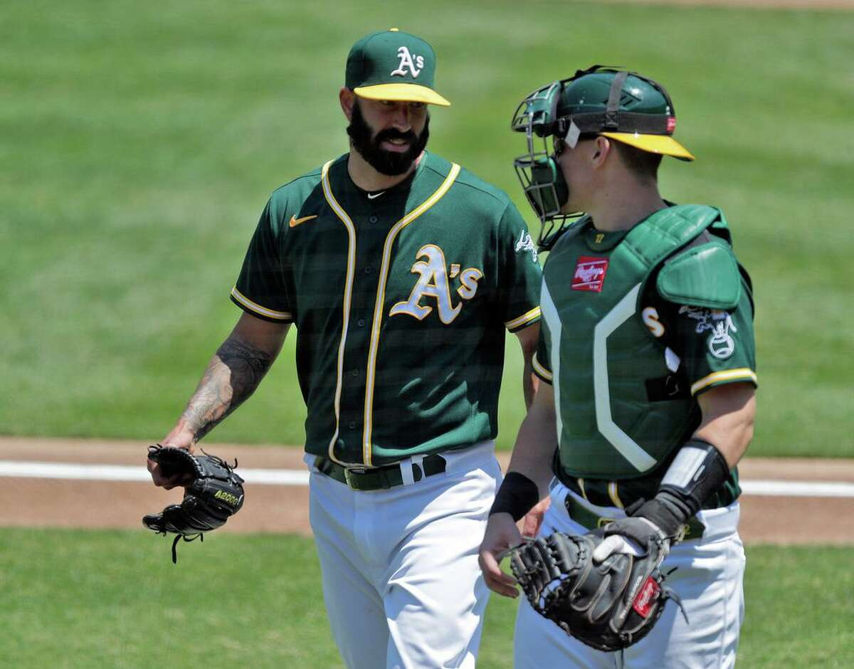 A's starter Mike FIers (50) and catcher Sean Murphy (12) chat after the last out of the top of the first inning as the Oakland Athletics played the Los Angeles Angels of Anaheim at the Coliseum in Oakland, Calif., on Sunday, July 26, 2020.