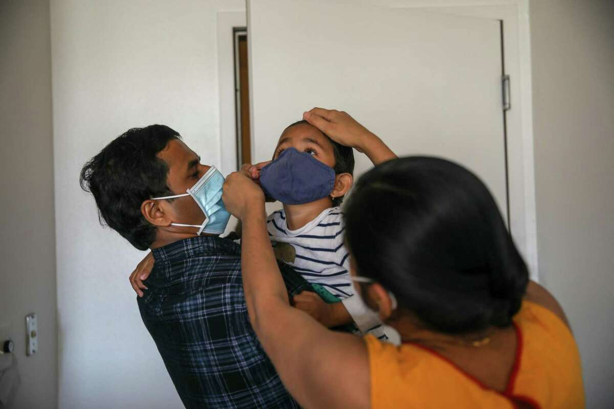 Dipali Suryamanshi puts a mask on son Prathamesh, 3, as her husband, San Francisco scientist Rahul Suryawanshi, holds him before heading outdoors in San Francisco. Many of Rahul Suryawanshi's relatives became infected with the coronavirus in India.