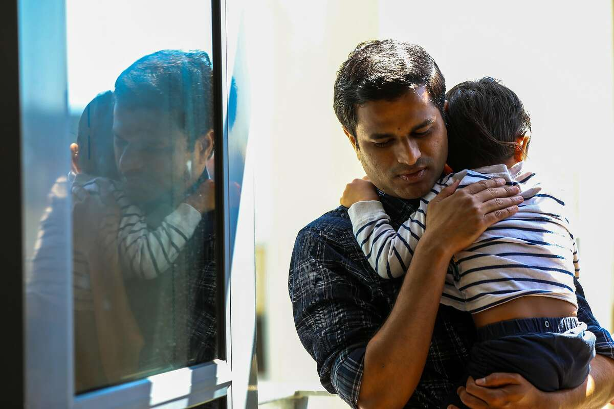 Rahul Suryawanshi, 36, holds his son Prathamesh, 3.5, at home on Wednesday, April 28, 2021, in San Francisco, Calif. Suryawanshi is a scientist at the Gladstone Institutes who studies the coronavirus in mice. His parents, grandmother, brother, cousins and 3-month-old niece all became infected with the virus, and most ended up in the hospital. Suryawanshi's 54-year-old mother is still in intensive care and he worries constantly about the oxygen supply constraints in India now.