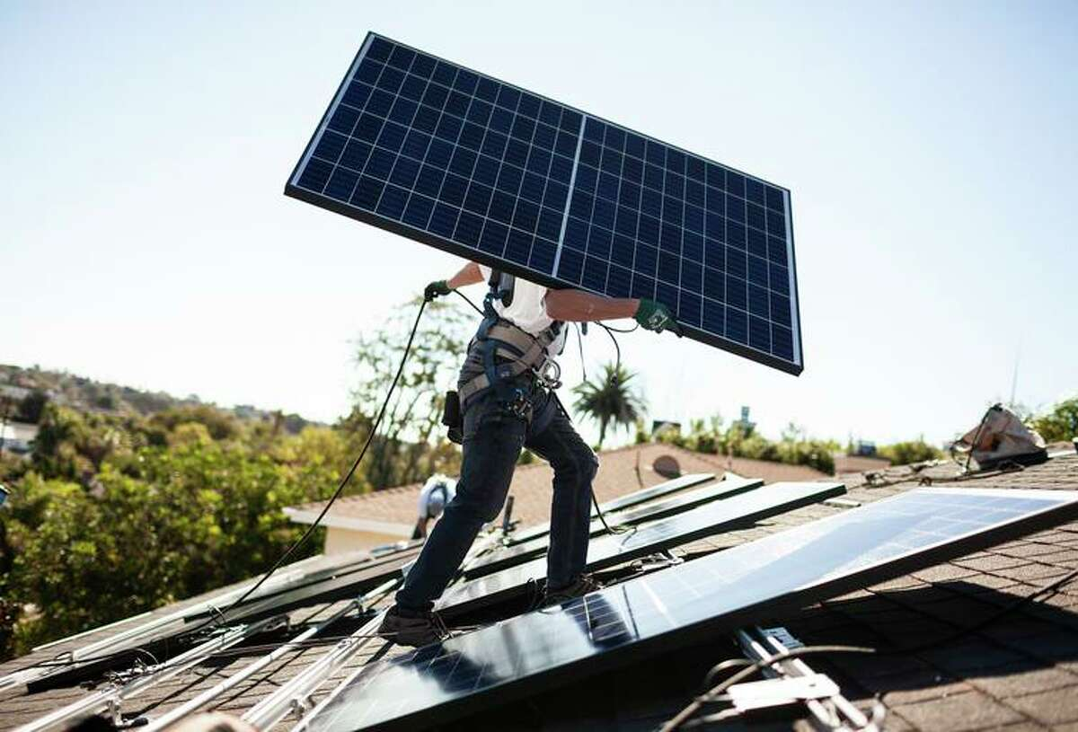 A Sunrun installer carries a solar panel into place at a customer's home in Carlsbad. A new app will make it easier for homeowners to acquire permits to install solar panels.