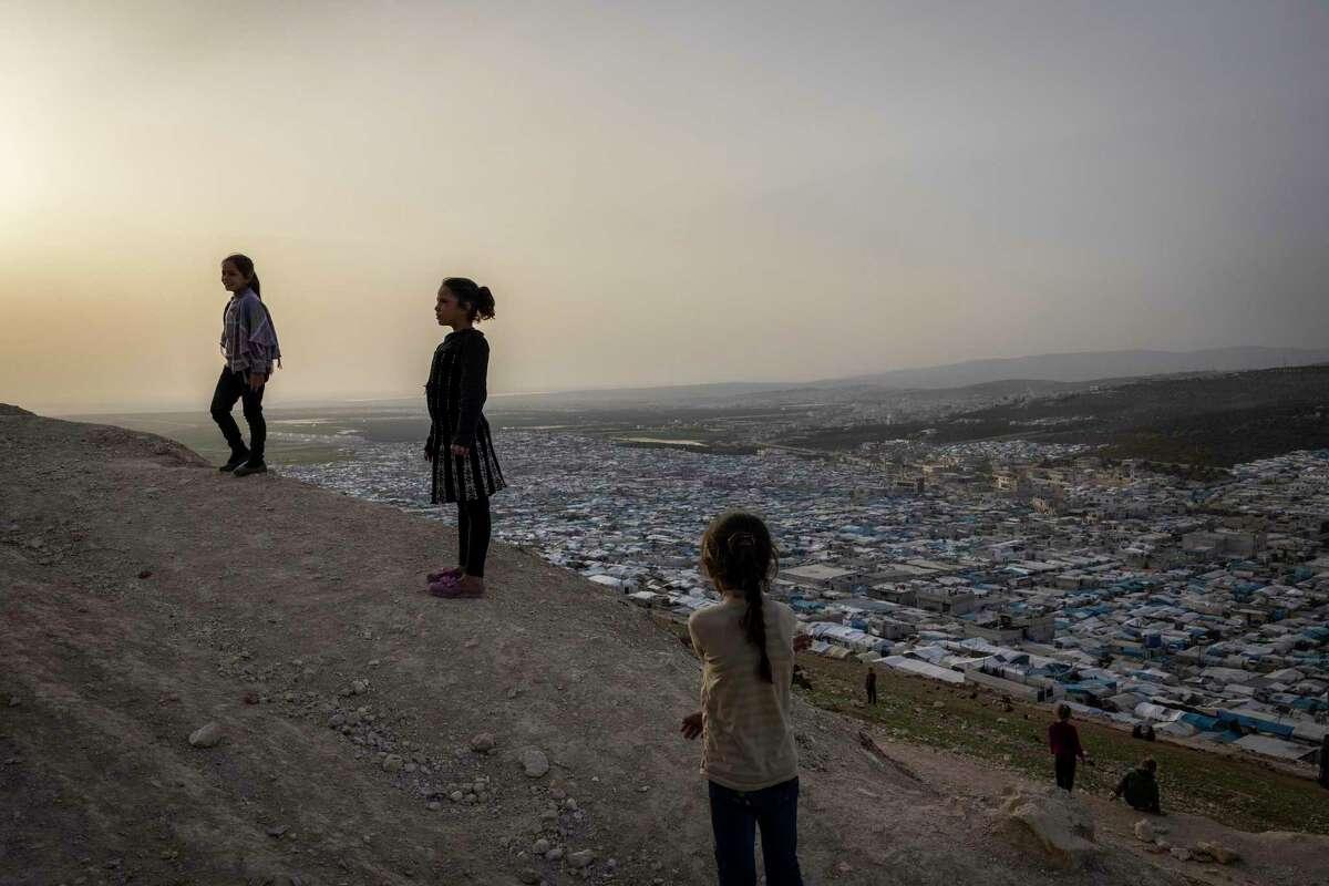 Children play on a hillside above a refugee camp in Syria. President Joe Biden should raise the refugee cap.