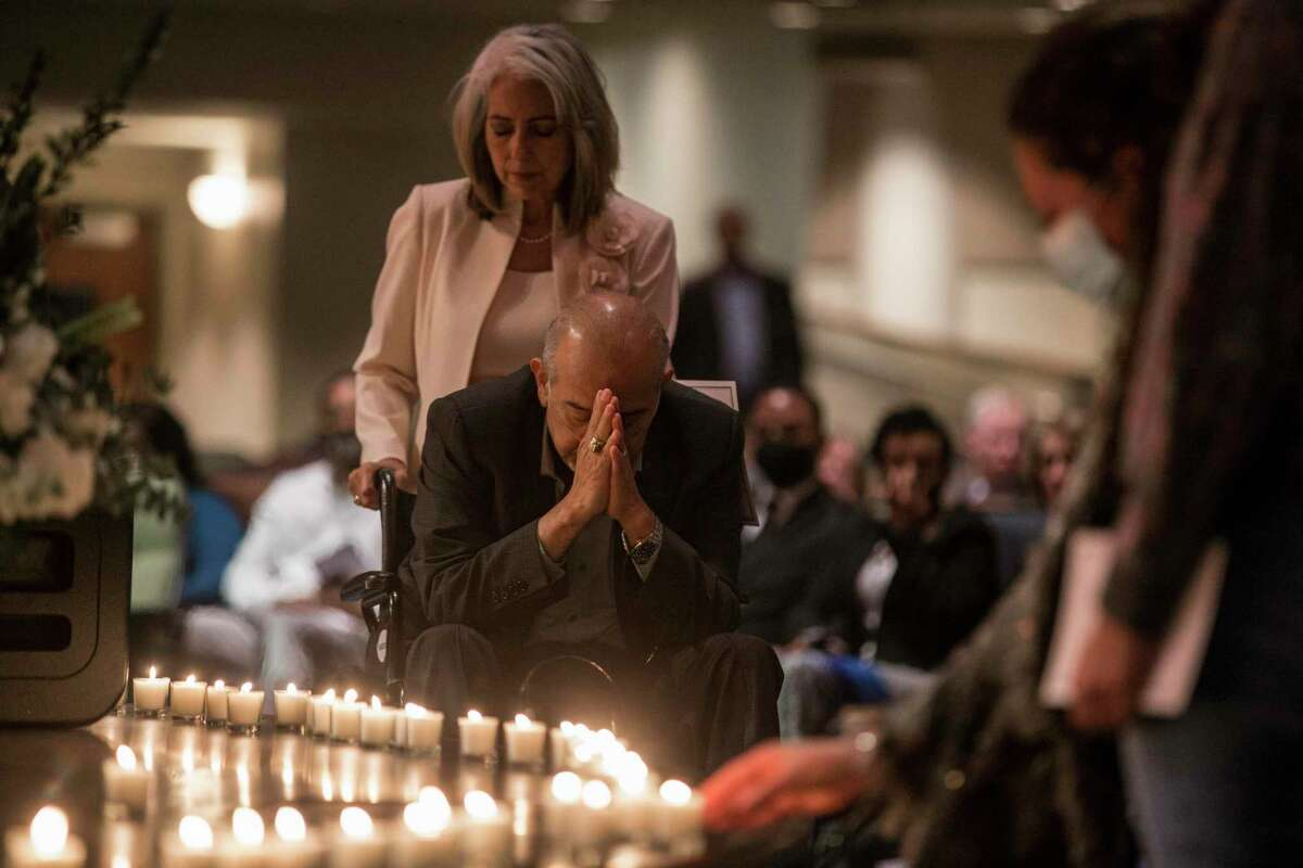 """People pray for loved ones lost during a """"COVID service of remembrance"""" at Champion Forest Baptist Church Sunday, April 18, 2021 in Houston. The church's service was for all who lost someone during the COVID-19 pandemic, but did not have the normal way to grieve in a full memorial service."""