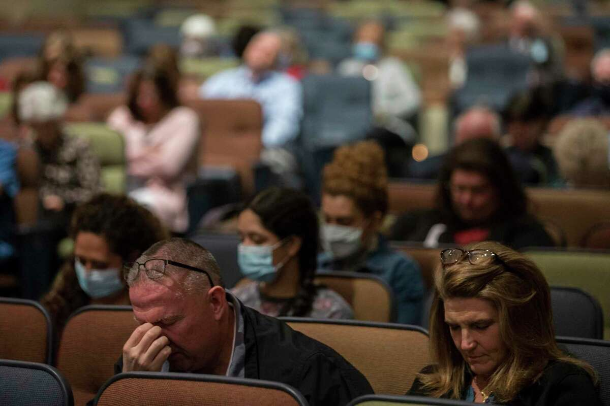 """Parishioners bow their heads in prayer during a """"COVID service of remembrance"""" at Champion Forest Baptist Church Sunday, April 18, 2021 in Houston. The church's service was for all who lost someone during the COVID-19 pandemic, but did not have the normal way to grieve in a full memorial service."""