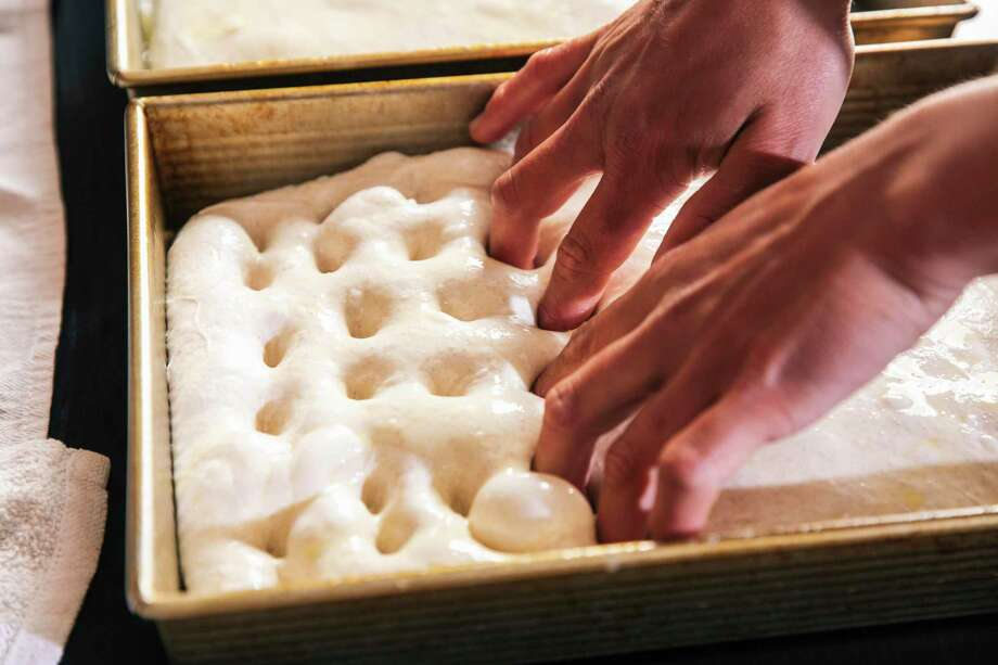 Armin Chan, founder of Weirdough Focaccia and a line cook at Mister Jiu's, dimples the focaccia dough at his home in S.F. Photo: Stephen Lam / The Chronicle / San Francisoc Chronicle