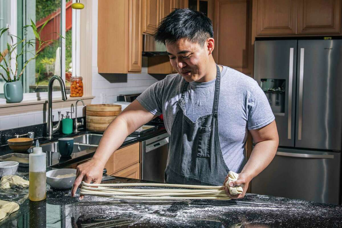 William Lim Do, founder of Lao Wai Noodles and former sous chef at Mister Jiu's, prepares to pull Da Kuan, or large width noodle, at his home in Daly City, Calif. Sunday, April 18, 2021.