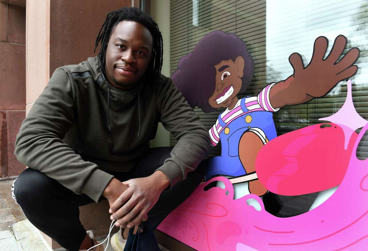 Artist Isaac Bloodworth of New Haven is photographed next to the character, Joy, he created on display as part of a larger mural at City Hall in New Haven on April 16, 2021.