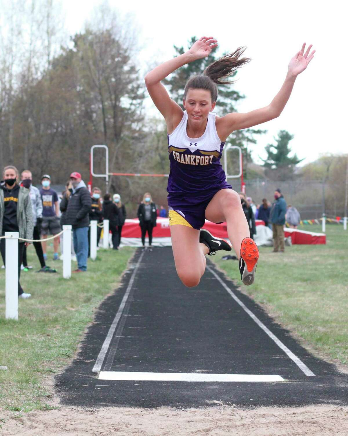 Grace Wolfe flies through the air in the long jump on April 28. (Robert Myers/Record Patriot)