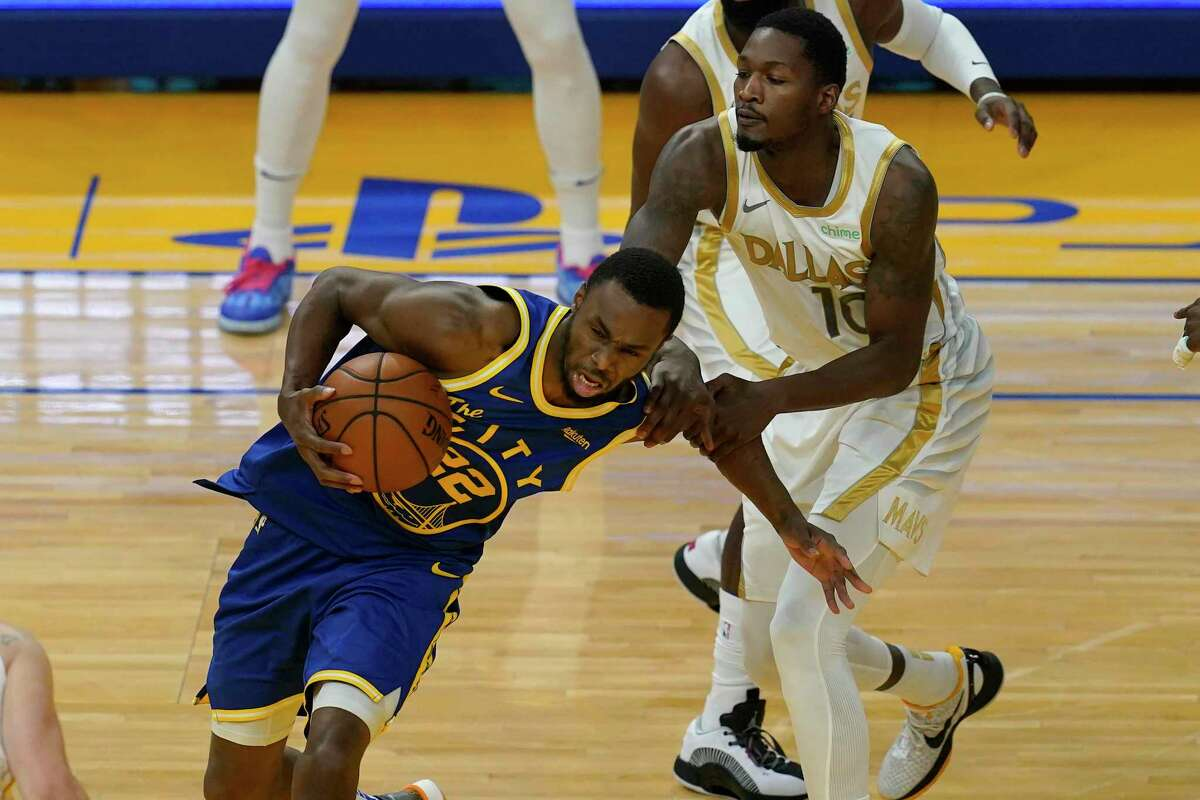 Golden State Warriors forward Andrew Wiggins (22) drives against Dallas Mavericks forward Dorian Finney-Smith (10) during an NBA basketball game in San Francisco, Tuesday, April 27, 2021. (AP Photo/Jeff Chiu)