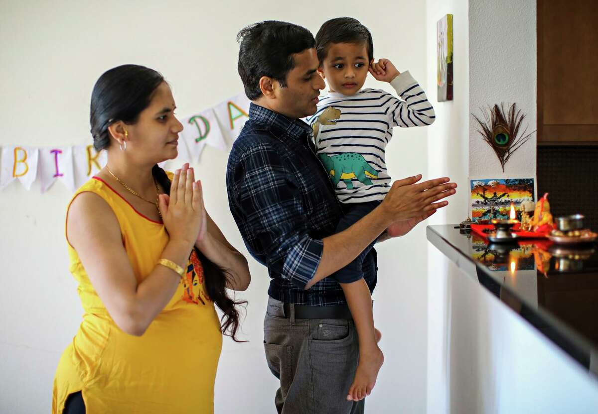 Dipali (left) and Rahul Suryawanshi pray with their son, Prathamesh, 3, in their San Francisco home. Rahul Suryawanshi's mother was in intensive care and died this week from COVID-19. He worries constantly about the oxygen supply constraints in India now.