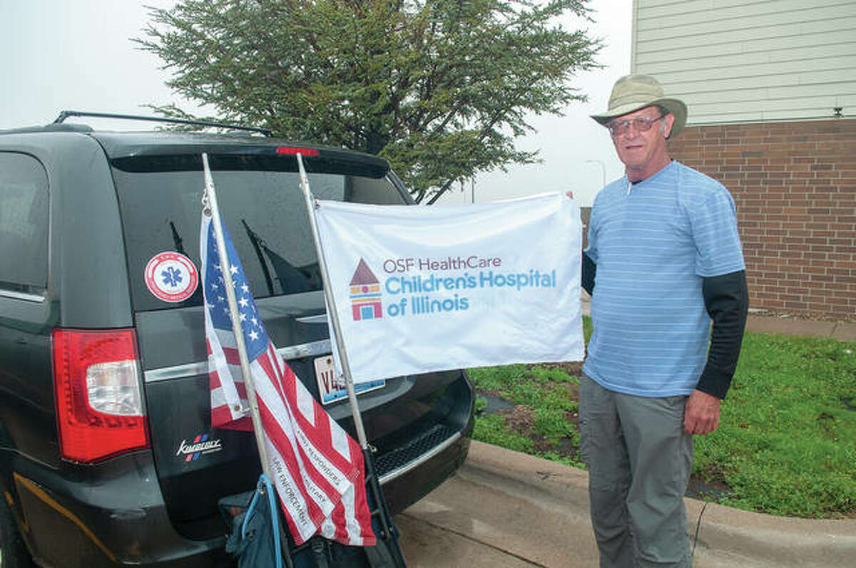 Tom Brewer holds up one of two flags that fly above him as he walks across Illinois. By the time he reaches Peoria, Brewer - who passed through Jacksonville on Wednesday and into Thursday - will have walked 526 miles over the past four years to raise awareness for children's hospitals.