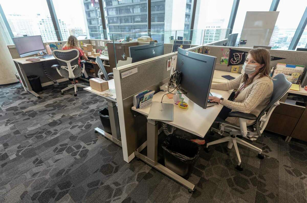 Jessica Faur, right, uses a single, wired connection Wednesday, April 28, 2021, to connect her laptop, on desk, to the Frost Bank offices on the 10th floor of the new Frost Bank tower is seen Wednesday, April 28, 2021. Colleague Brenda Trevino works at her desk in the background.
