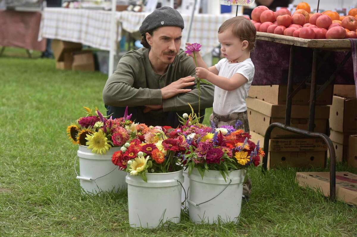 Ocean Casey, 18 months, of New Milford, examines a flower for sale, at the New Milford Farmers Market, with his father Tim Casey, on Saturday morning, September 1, 2018, in New Milford, Conn.