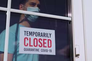 TEMPORARILY CLOSED: sign on a door. Business owner in medical mask puts a CLOSED sign on the front door due to the coronavirus COVID19 pandemic. Small business incurs losses during the coronavirus.
