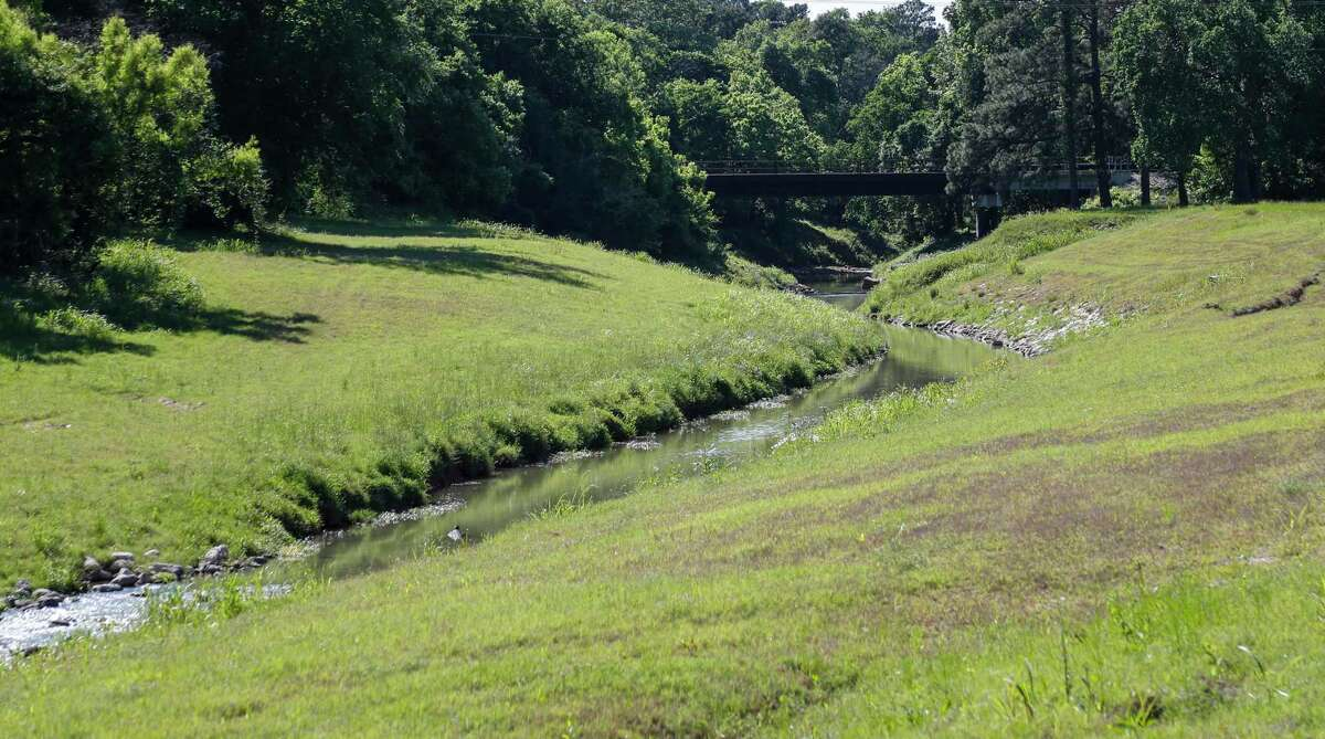 A section of Halls Bayou near Wayside Drive and the Northeast Family YMCA, Wednesday, April 21, 2021, in Houston. A year to the day after Hurricane Harvey made landfall, Harris County voters approved a $2.5 billion flood bond, the single-largest investment in storm protection in county history. Elected and Flood Control District officials pitched the program as a down payment on securing Houston's future, a serious commitment by taxpayers that would convince the state and federal governments to chip in billions more. But that outside investment has not come through, at least not yet, and the county budget office last month announced a $1.4 billion shortfall in funding for current projects. In the near-term, Commissioners Court may need to raise taxes or issue a new bond proposal, which voters may be wary to support if they feel hoodwinked by the first one. Longer-term, local leaders have secured nowhere close to the more than $30 billion engineers say is needed to fully protect the county from 100-year storms. Experts say that H ouston, the largest metro area on the Gulf Coast and one that has suffered four major floods in the past six years, has a unique opportunity to show how a region can transform to handle climate change. So far, it has few completed efforts to show for its efforts since Harvey flooded more than 200,000 homes.