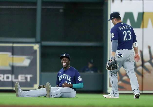Seattle Mariners center fielder Taylor Trammell (20) smiles after sliding to make a catch on Houston Astros Carlos Correa's fly out to end the ninth inning of an MLB baseball game at Minute Maid Park, Thursday April 29, 2021, in Houston. Photo: Karen Warren, Staff Photographer / @2021 Houston Chronicle