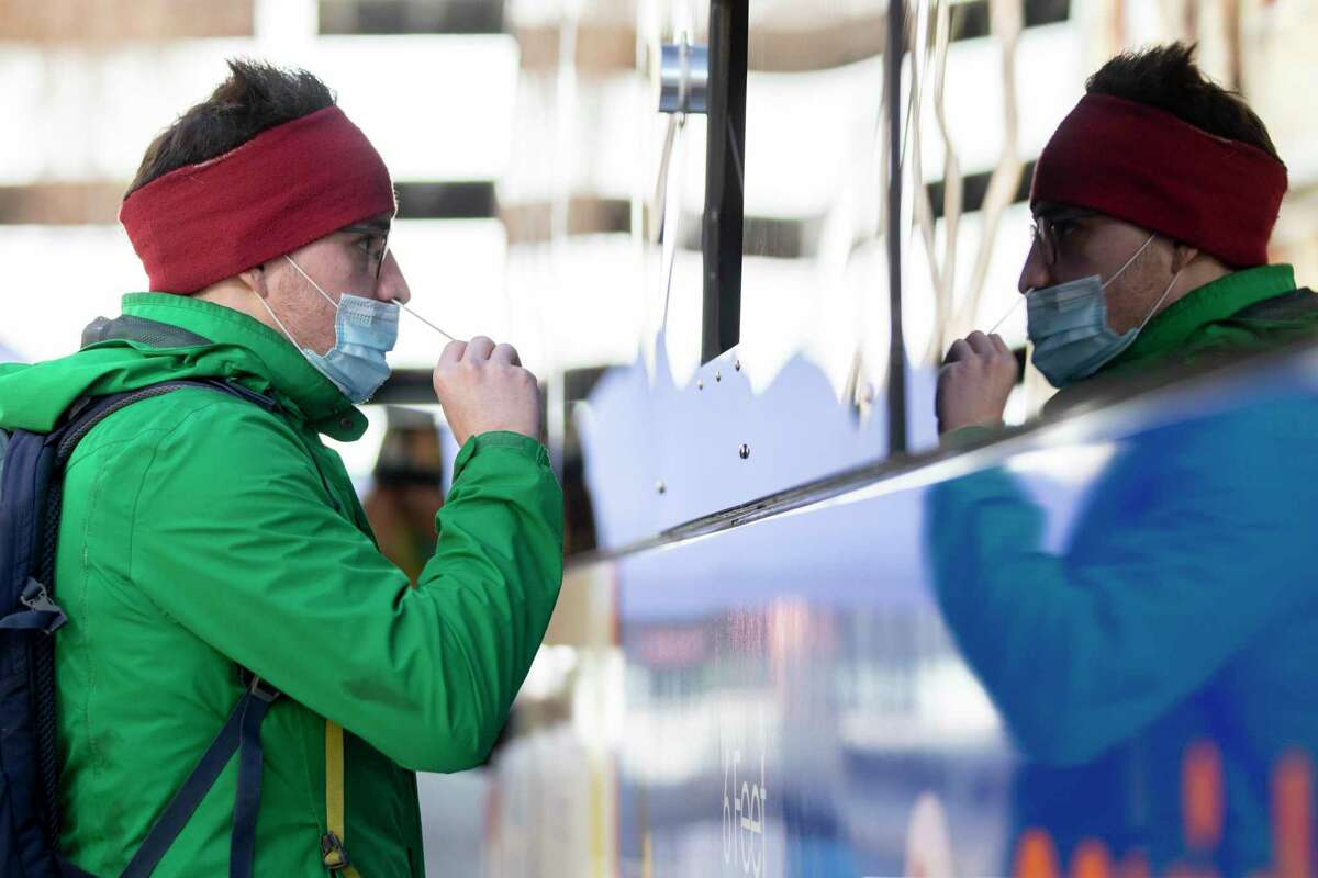 Sebastian Sandl gets a COVID-19 nose swab test at the BusTest Express mobile test site in Berkeley, Calif. Tuesday, January 26, 2021. Even vaccinated people still need to get tested in some situations.