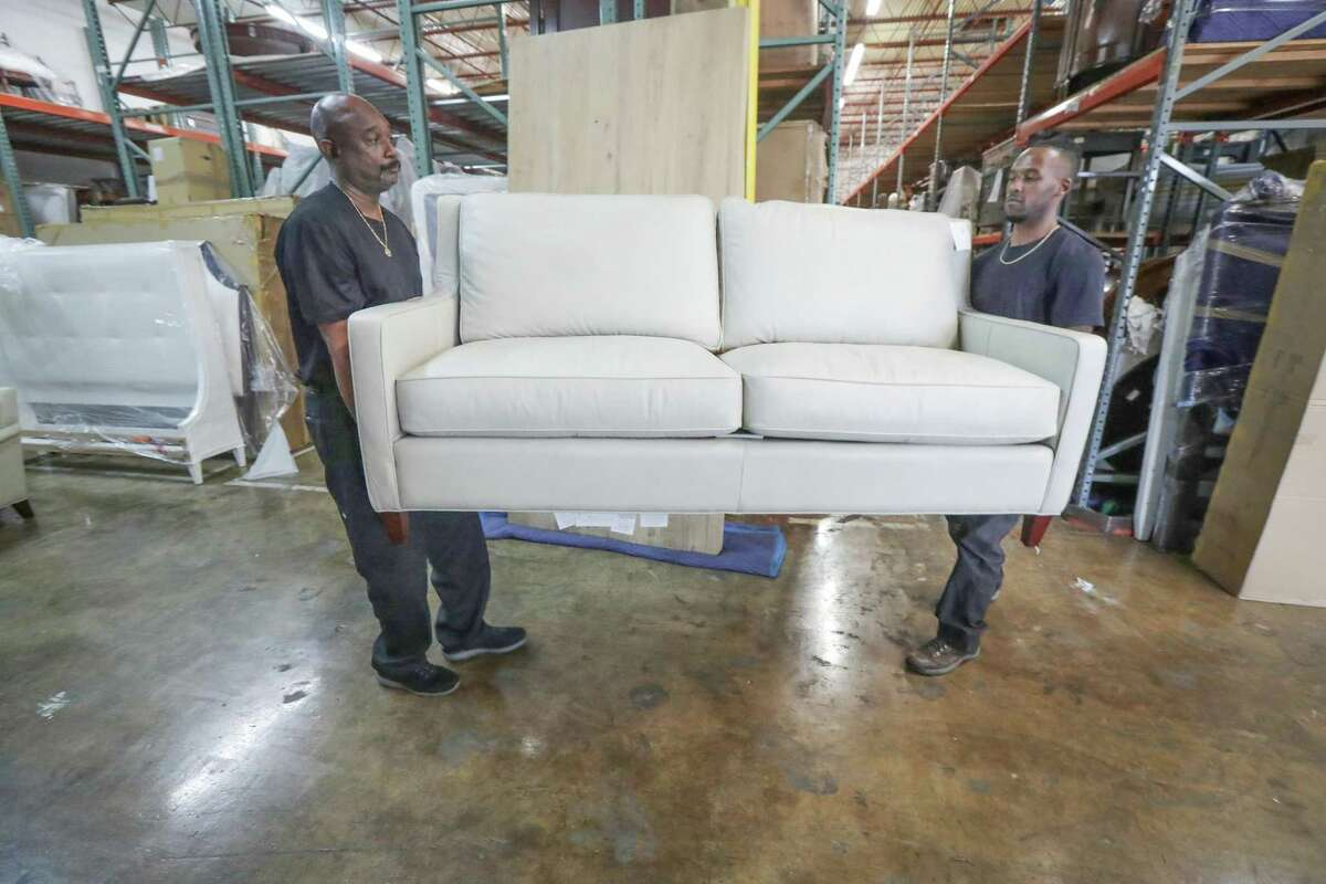 Meredith O'Donnell Fine Furniture employees Earl Francis (left) and Surrell Mayfield move furniture in the company's warehouse Friday, April 23, 2021, in Houston.