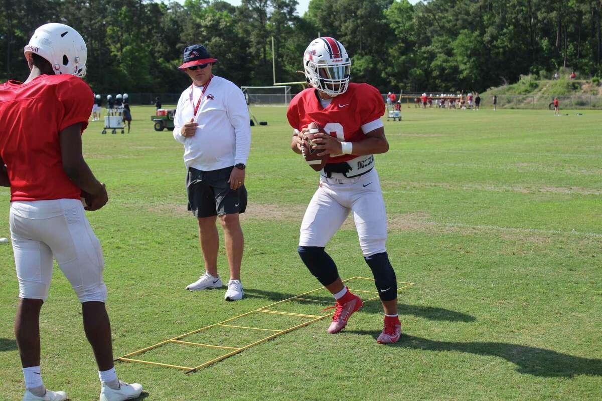 Atascocita junior quarterback Gavin Session working through quarterback drill with coach Craig Stump.