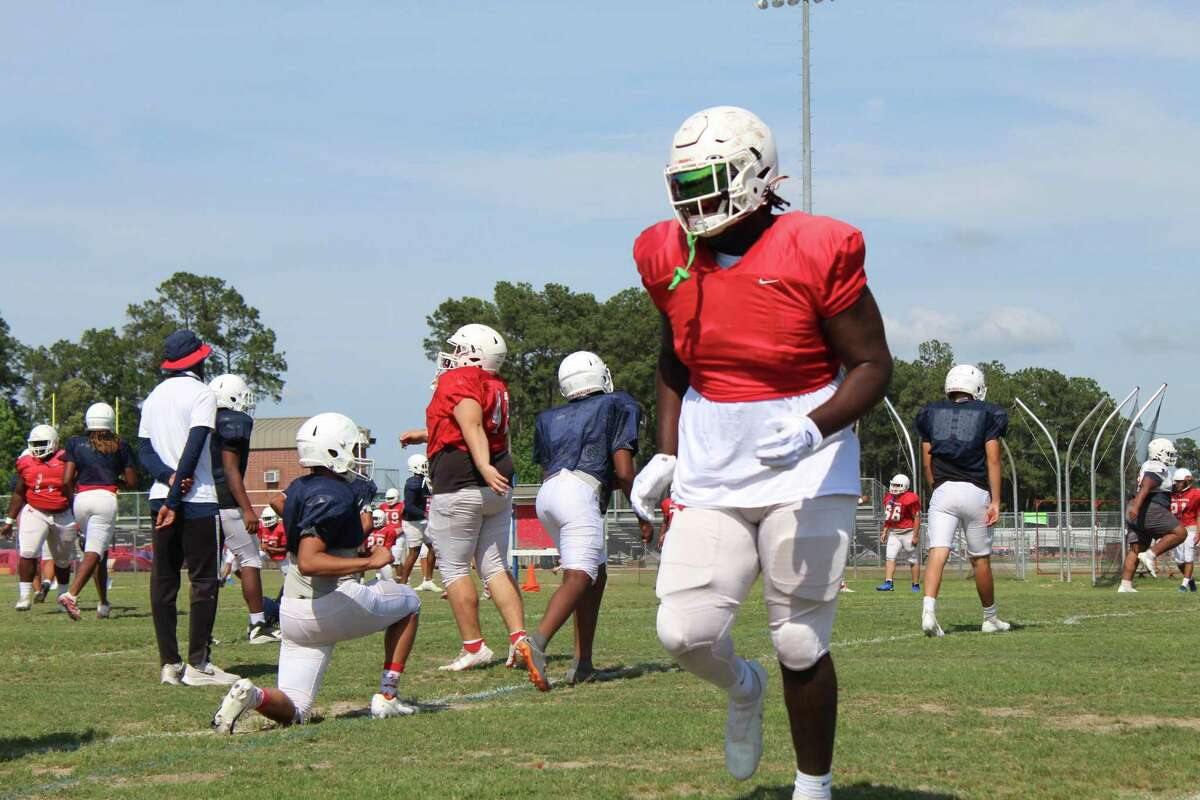 Atascocita offensive linemen Kam Dewberry stretching before practice with his teammates.