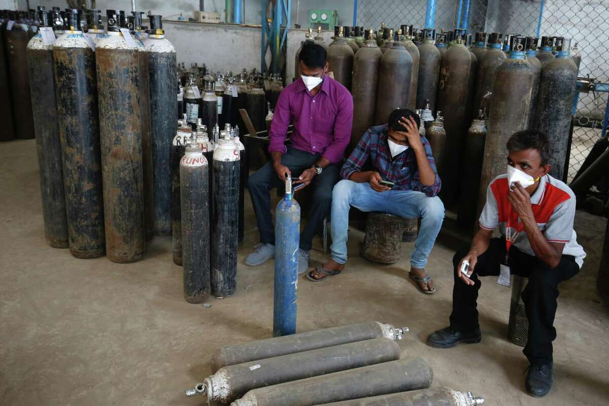 People wait to get their oxygen cylinders filled inside in Bengaluru, India. With coronavirus infection rates rising above 350,000 daily, members of the Bay Area's Indian American diaspora have found themselves working desperately to mobilize life-saving oxygen or demanding American aid.