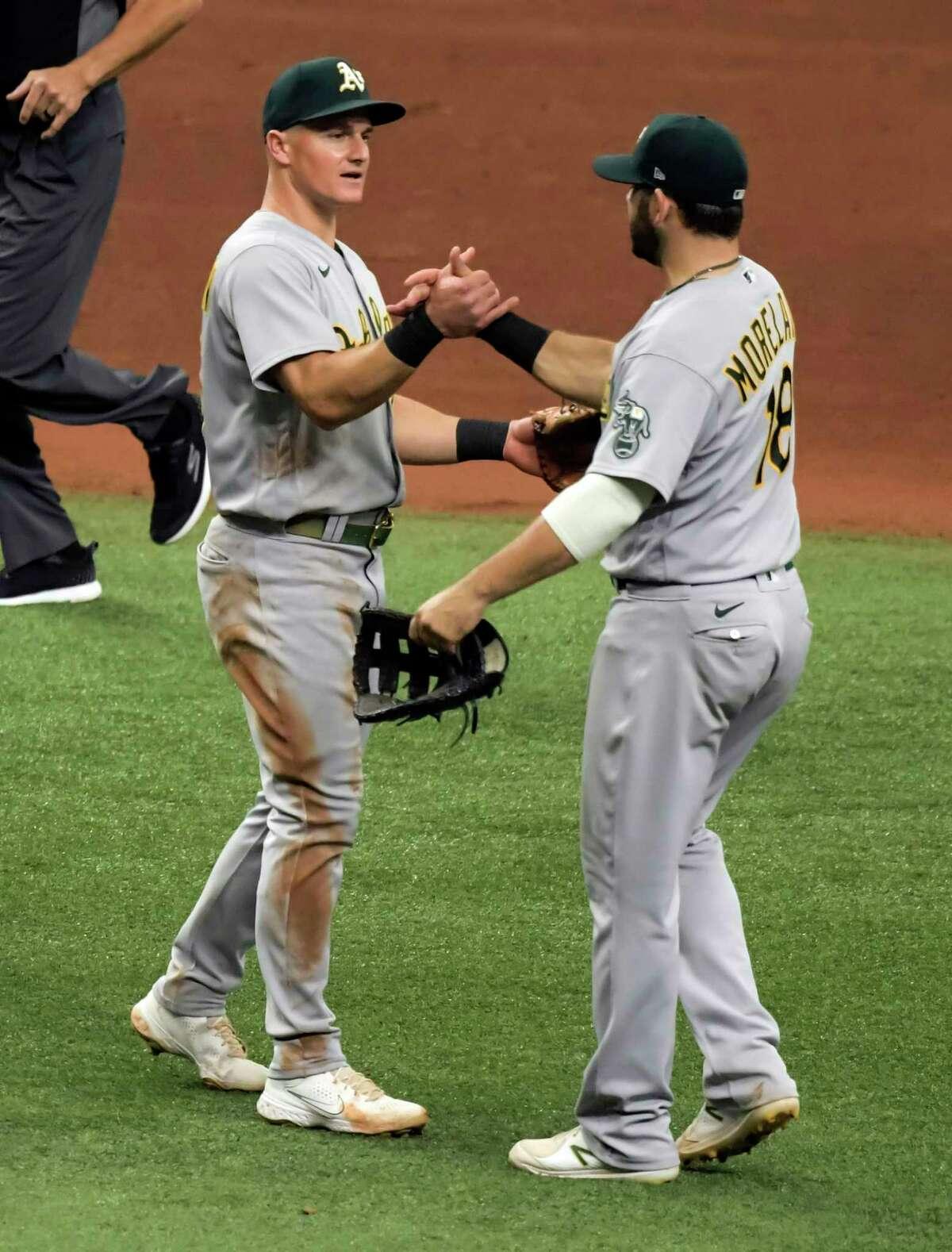 Corner infielders Matt Chapman (left) and Mitch Moreland celebrate the A's win over Tampa Bay.