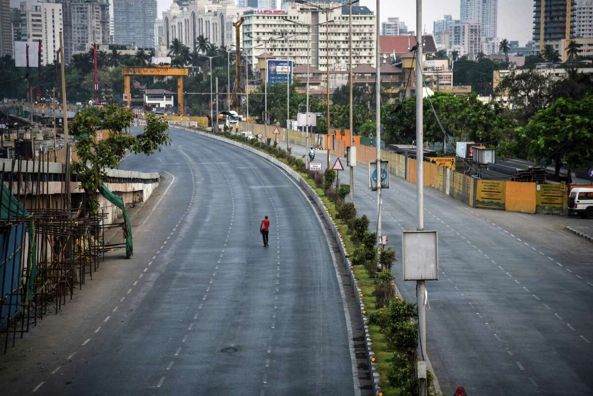 MUMBAI, INDIA - APRIL 29: A pedestrian walks along a near-deserted street during a lockdown imposed to try and contain the spread of Covid-19 on April 29, 2021 in Mumbai, India. With recorded cases crossing 380,000 a day and 3000 deaths in the last 24 hours, India has more than 2 million active cases of Covid-19, the second-highest number in the world after the U.S. A new wave of the pandemic has totally overwhelmed the country's healthcare services and has caused crematoriums to operate day and night as the number of victims continues to spiral out of control. (Photo by Fariha Farooqui/Getty Images) *** BESTPIX ***