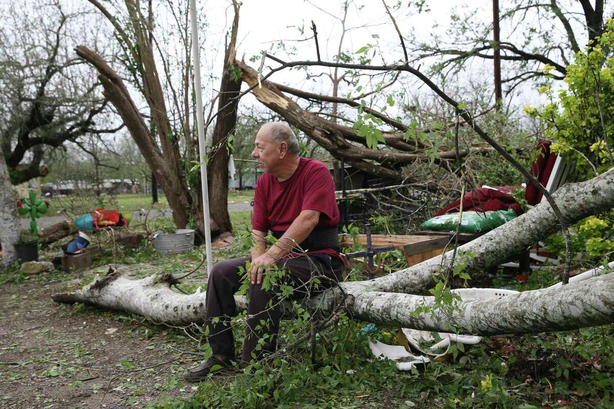 Emilio Gonzales sits on a down tree at a friend's house in D'Hanis, Texas, Thursday, April 29, 2021. Large hail and a possible tornado hit the area Wednesday night into early morning on Thursday causing widespread damage. The same storms dumped heavy rain in San Antonio.