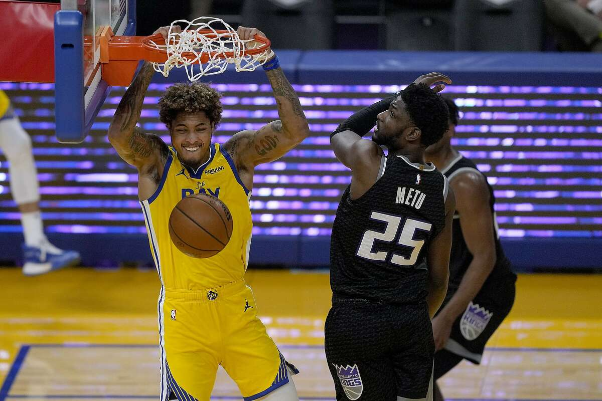 Golden State Warriors guard Kelly Oubre Jr. (12) dunks against Sacramento Kings forward Chimezie Metu (25) during the first half of an NBA basketball game on Sunday, April 25, 2021, in San Francisco. (AP Photo/Tony Avelar)