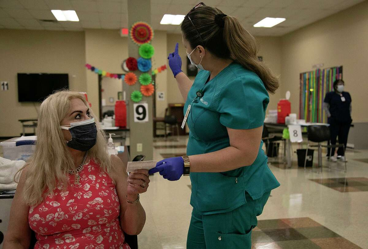 LVN Melissa Reyes, right, hands Elsa Hernandez her vaccination card and directs her to the observation area after giving her the Johnson & Johnson COVID-19 vaccine Wednesday, April 28, 2021, at WellMed's vaccine clinic at Treviño López Senior One-Stop Center.