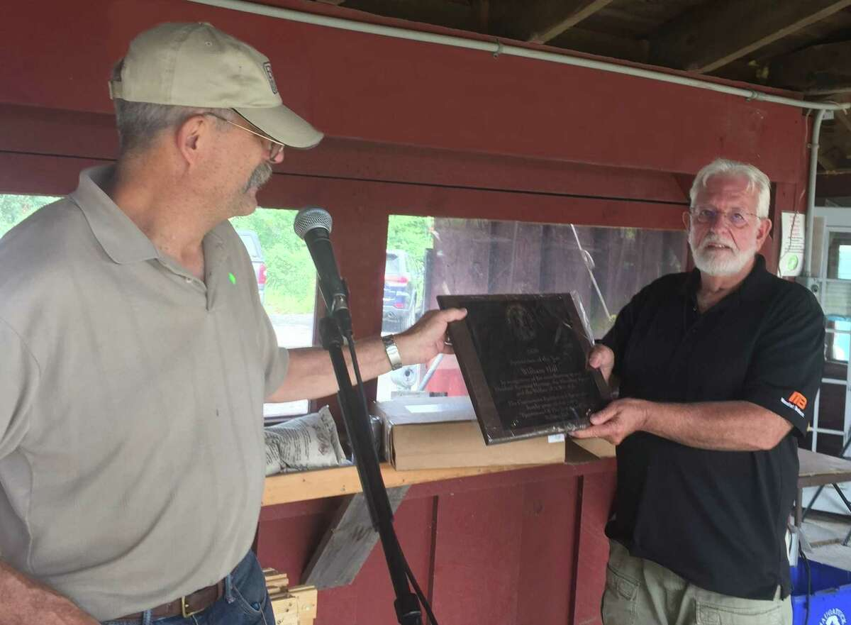 Tom Andersen, left, a member of the Northwestern CT Sportsmen's Association, presents William Hill with the Peter Holms Trophy for Sportsman of the Year at the organization's 93nd annual sportsmen's awards event.