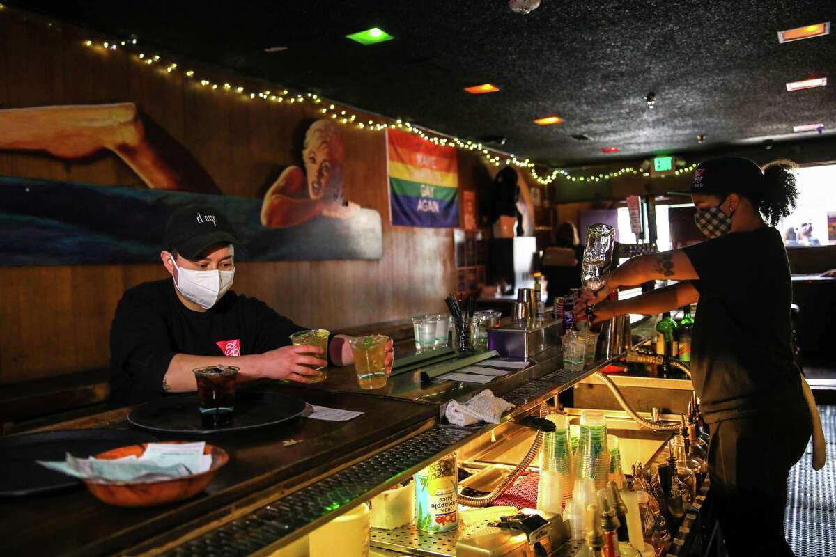 Cynthia Martinez, manager, left, and Jasmine Johnson, a bartender, work at El Rio in San Francisco. Bars that don't serve food will likely be able to open indoors for the first time next week.