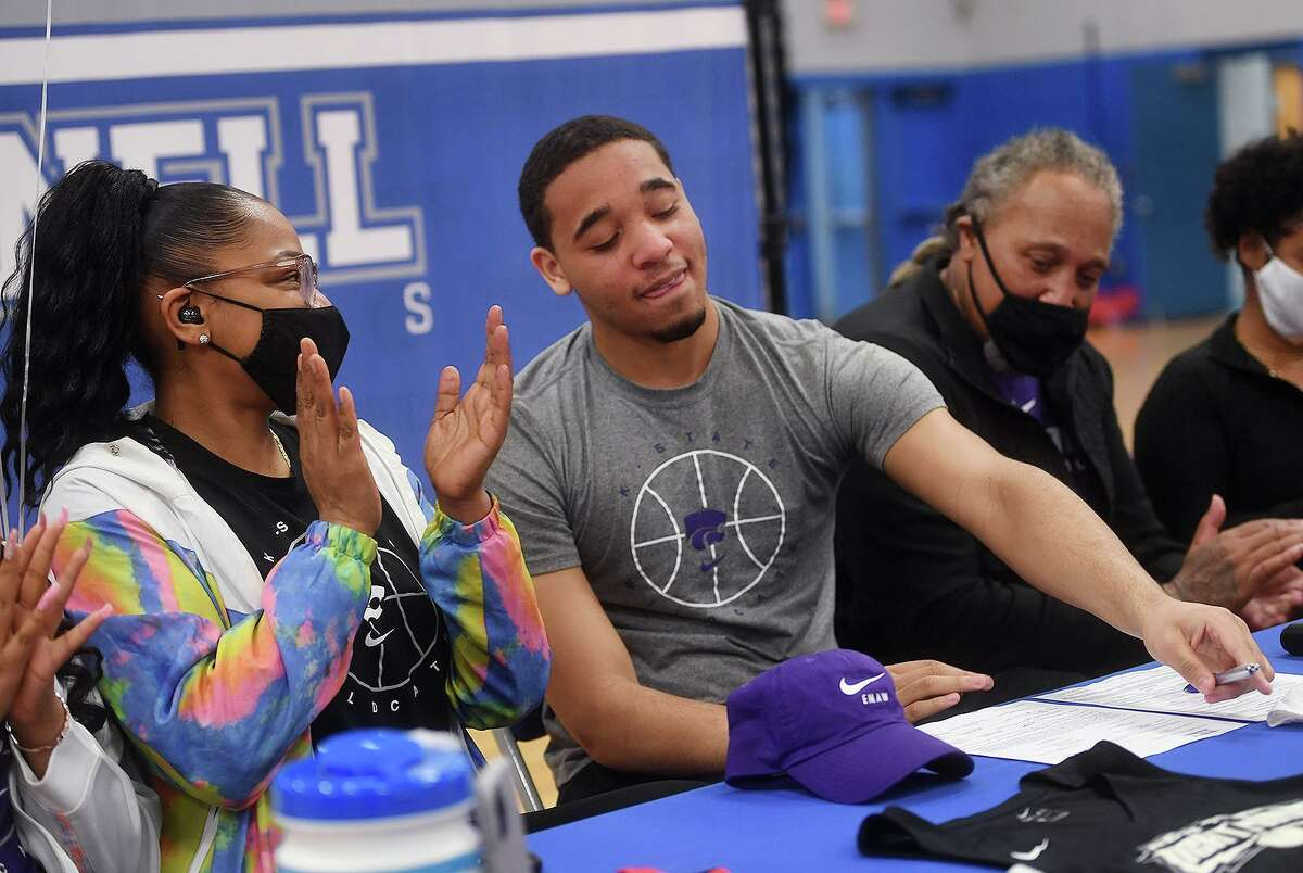 Flanked by his parents Tonya Pooser, left, and Bret Edwards, former Bunnell basketball player Maximus Edwards signs his National Letter of Intent to attend Kansas State on Thursday.