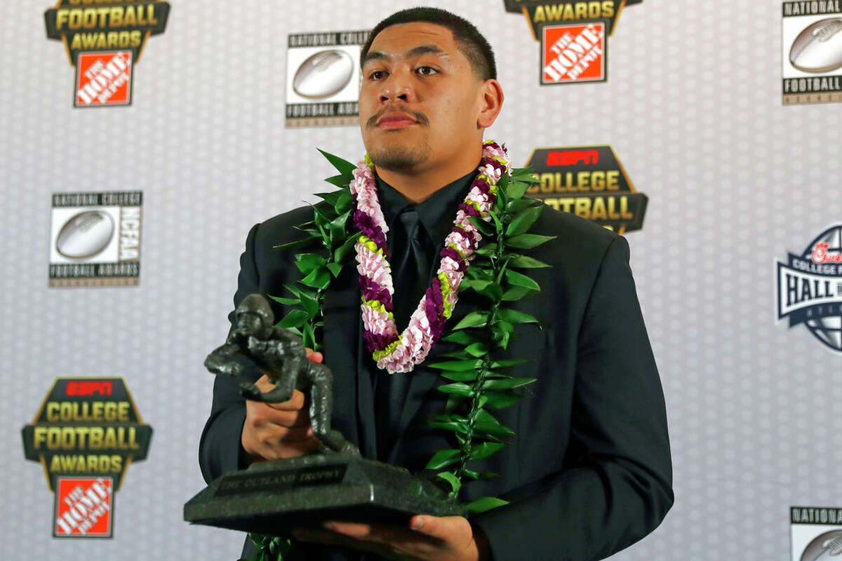 FILE - In this Dec. 12, 2019, file photo, Oregon's Penei Sewell poses with Outland Trophy for being the nation's best interior lineman, in Atlanta. Sewell is a likely first round pick in the NFL Draft, April 29-May 1, 2021, in Cleveland.(AP Photo/, File)