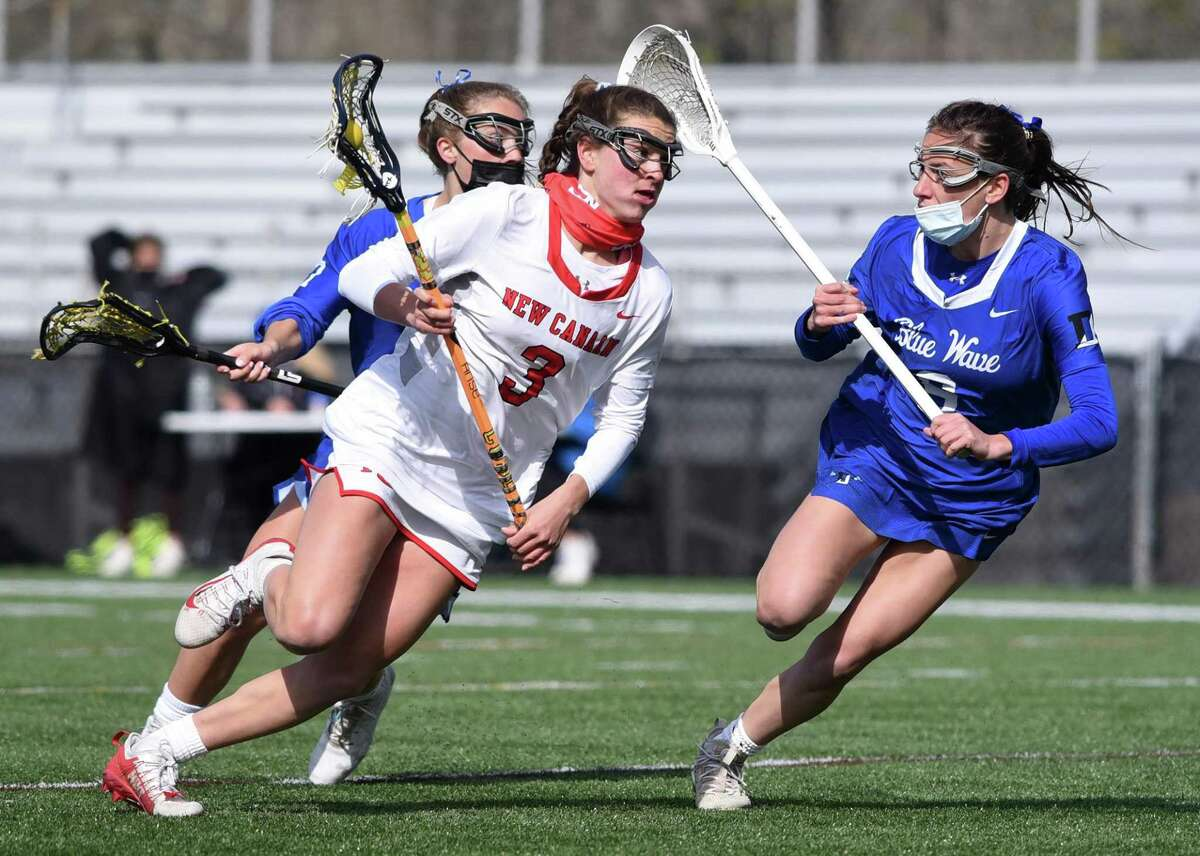 New Canaan's Dillyn Patten (3) drives to the goal while Darien's Sam Barlow (3) defends during a girls lacrosse game at Dunning Field on Thursday, April 22, 2021.