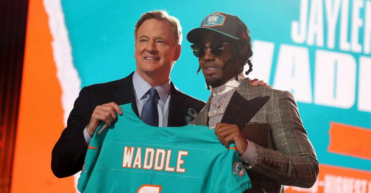 Jaylen Waddle poses with NFL Commissioner Roger Goodell onstage after being selected with the sixth pick by the Miami Dolphins during round one of the 2021 NFL Draft at the Great Lakes Science Center on April 29, 2021 in Cleveland, Ohio. (Photo by Gregory Shamus/Getty Images)
