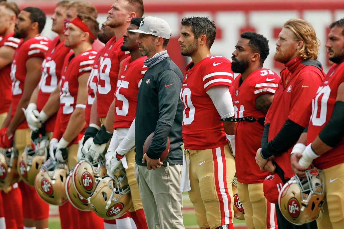 """San Francisco 49ers' head coach Kyle Shanahan, Jimmy Garoppolo and Raheem Mostert stand in end zone as """"Lift Up Every Voice"""" plays before Niners play Arizona Cardinals during NFL game at Levi's Stadium in Santa Clara, Calif., on Sunday, September 13, 2020."""