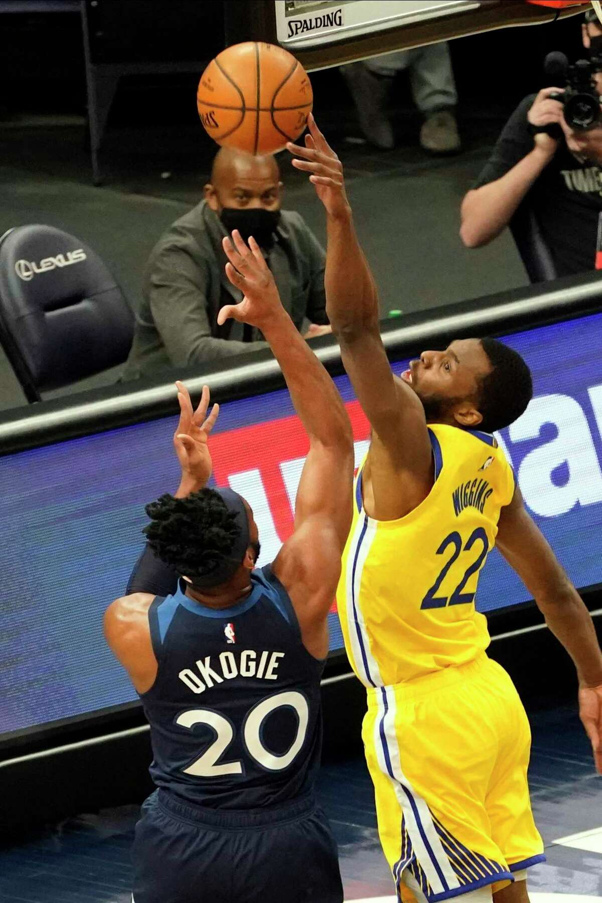 Golden State Warriors' Andrew Wiggins (22) tries to block a shot by Minnesota Timberwolves' Josh Okogie (20) in the first half of an NBA basketball game, Thursday, April 29, 2021, in Minneapolis. (AP Photo/Jim Mone)