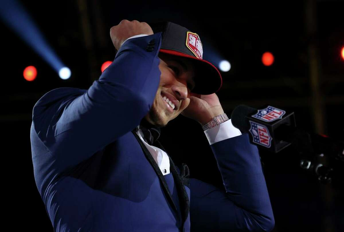 Trey Lance speaks puts on a 49ers cap after he was selected by the team as their top pick during the NFL draft in Cleveland.