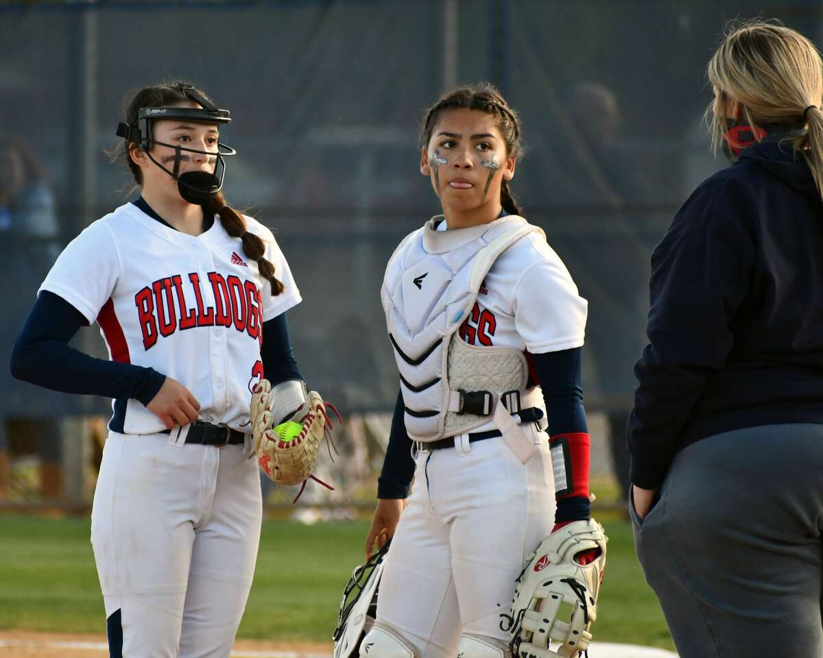 Pitcher Esme Lucio (left) and catcher Aaleah Rodriguez await a chat with pitching coach Kami Carnell in the first inning.