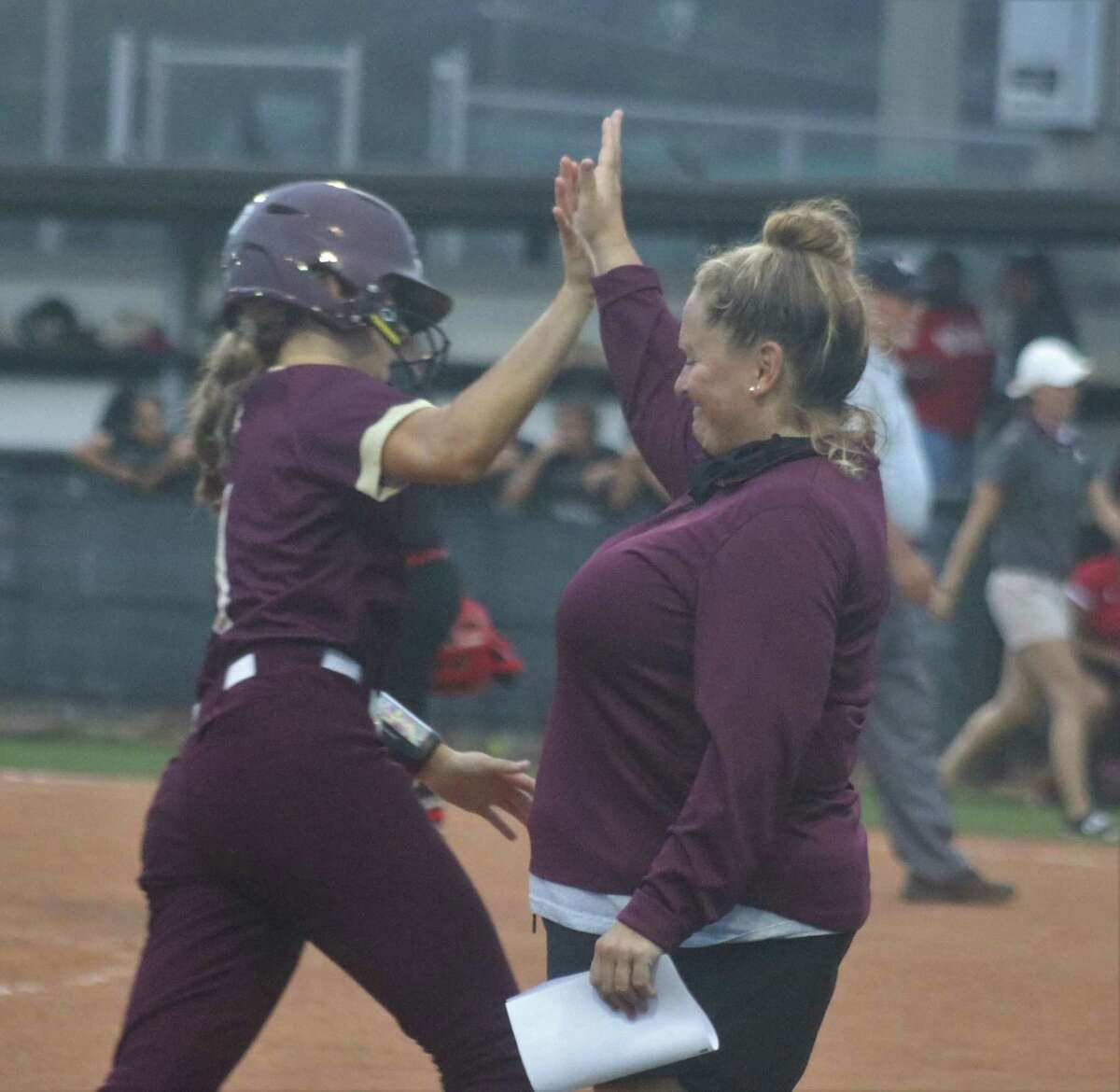 Deer Park head coach Amy Vidal greets Haidyn Hardcastle as she rounds third base after Hardcastle connected for a two-run homer in the fifth inning Thursday night.