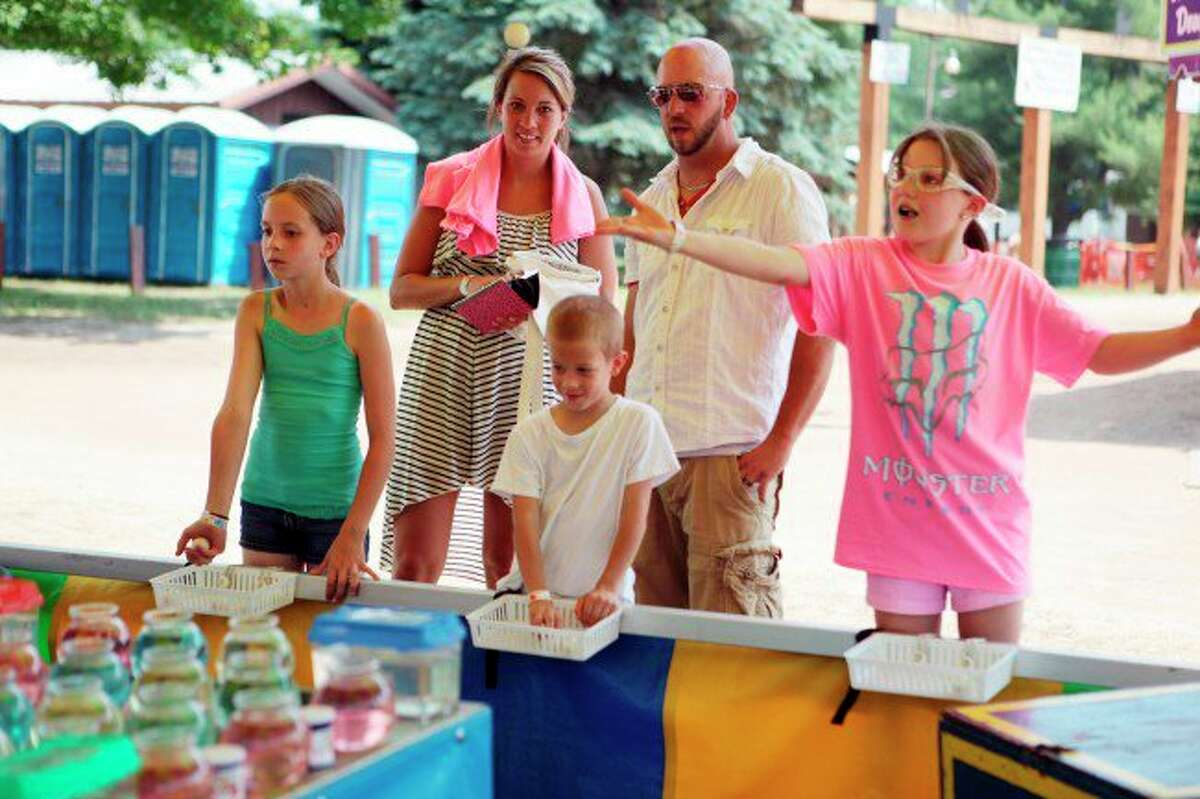 In this Star file photo, a family is pictured playing a carnival game at the Flea Roast and Ox Market Festival in Irons. Organizers have canceled this year's festival. (Star file photo)