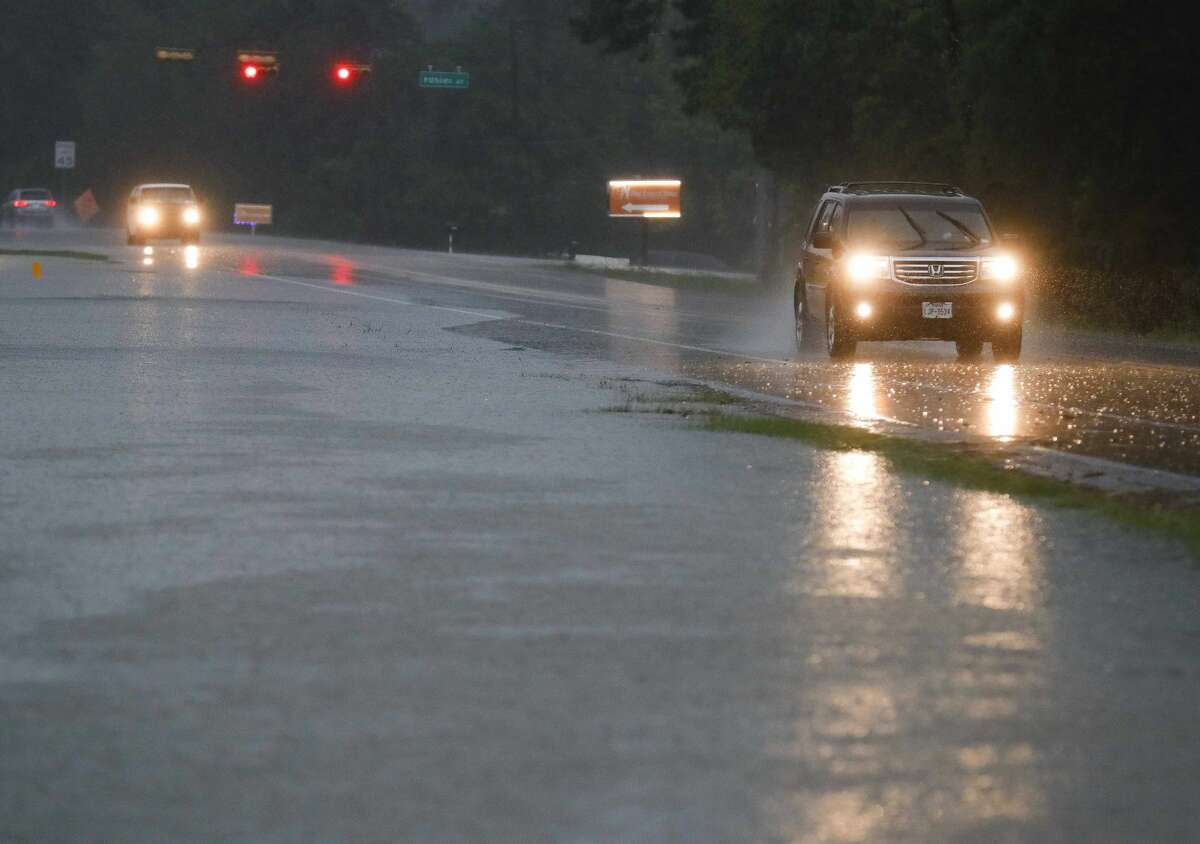 Vehicles drive down F.M. 1314 as heavy rains begin to flood portions of the road , Friday, April 30, 2021, in Conroe. Heavy rainfall moved into Montgomery County early Friday morning, prompting local officials to issue warnings about flooding and reminders to avoid driving into low lying areas.