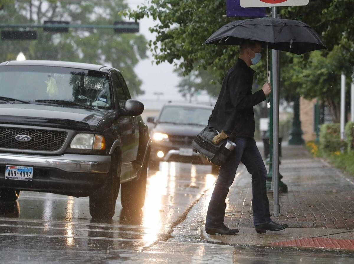 Montgomery County Assistant District Attorney Andrew James walks to work in the rain as heavy rains begin to flood portions of the road , Friday, April 30, 2021, in Conroe. Heavy rainfall moved into Montgomery County early Friday morning, prompting local officials to issue warnings about flooding and reminders to avoid driving into low lying areas.