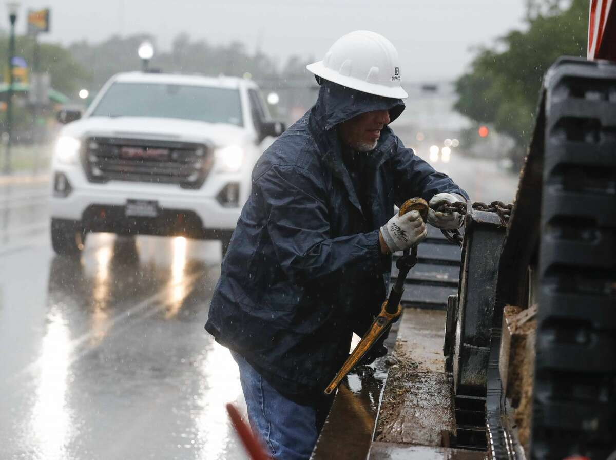 Joe Sandoval works to secure construction equipment as heavy rain falls in front of the site of Woodforest National Bank's 30,000 square-food office site, Friday, April 30, 2021, in downtown Conroe. Heavy rainfall moved into Montgomery County early Friday morning, prompting local officials to issue warnings about flooding and reminders to avoid driving into low lying areas.
