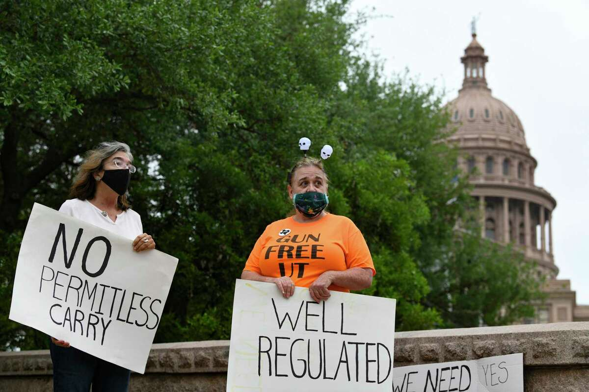 """Tracy Gehman, left, and a woman who identified herself as """"Lola"""" display their opposition to permitless gun carry as legislators take up the issue in the Texas Capitol on Thursday, April 15, 2021."""