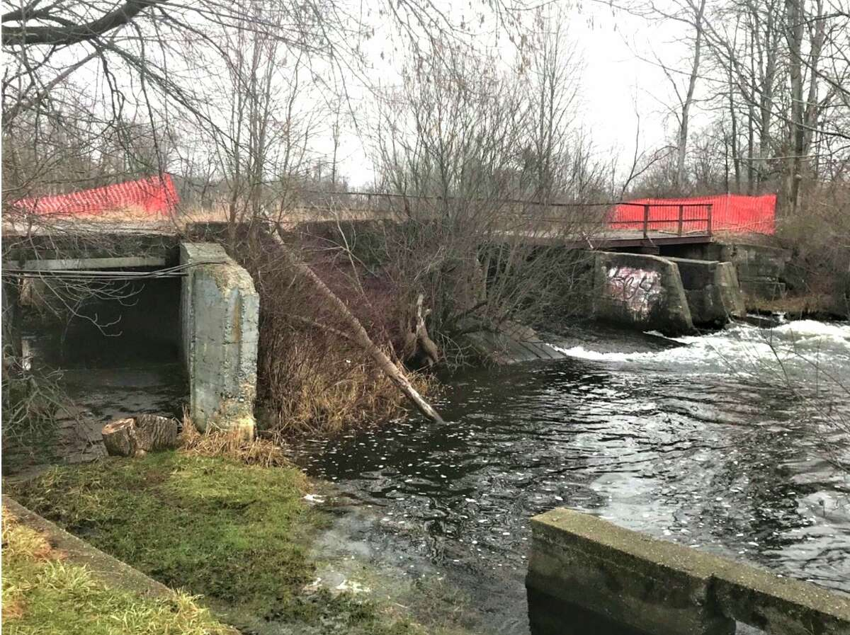 Altona Dam on the Little Muskegon River is deteriorating, blocking fish passage and impounding sediment on the Little Muskegon River. Orange snow fencing is to discourage pedestrian use of the aging, concrete structure. (Courtesy photo)